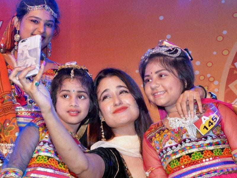 Bollywood actor Yuvika Choudhary clicks a selfie with kids who performed Garba at a Navratri function in Jabalpur. (PTI Photo)