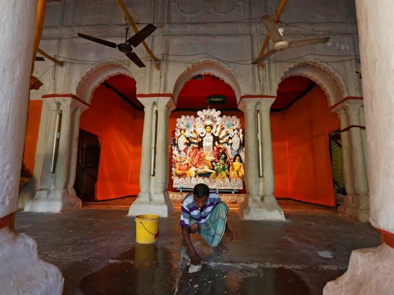 A worker cleans the floor after installing the idol of Goddess Durga at a platform inside a home in Kolkata, October 7, 2016. (REUTERS)