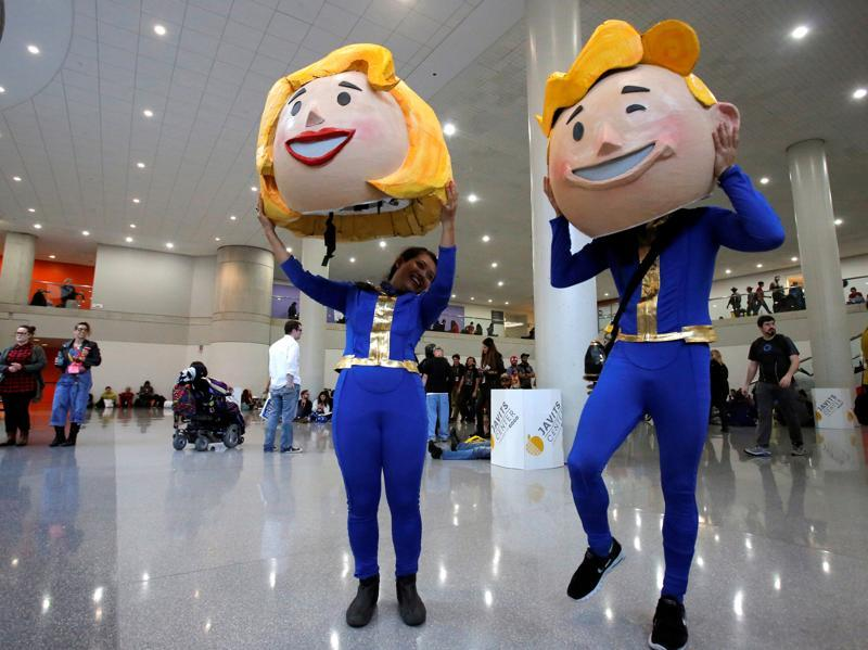 Participants Vanessa Pham and Adrian Chan remove their costumes of Vault Boy and Vault Girl at the event. (REUTERS)