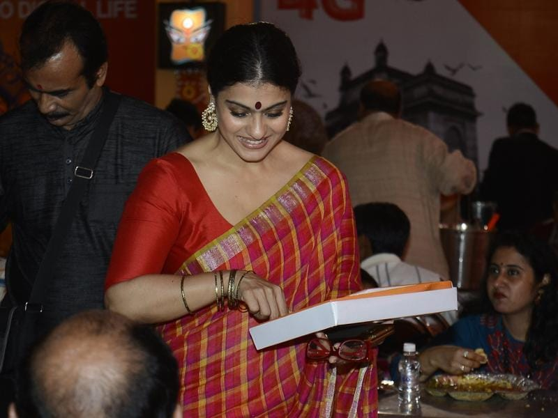 Kajol distributes sweets during the North Bombay Durga Puja celebrations in Mumbai on Oct. 8, 2016. (IANS)
