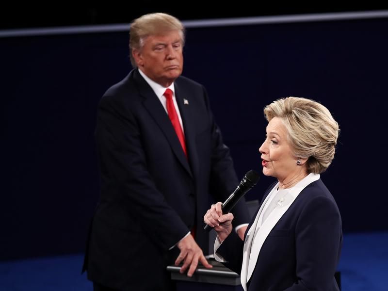Democratic presidential nominee and former secretary of state Hillary Clinton (right) speaks as Trump looks on during the town hall debate at Washington University. (AFP Photo)