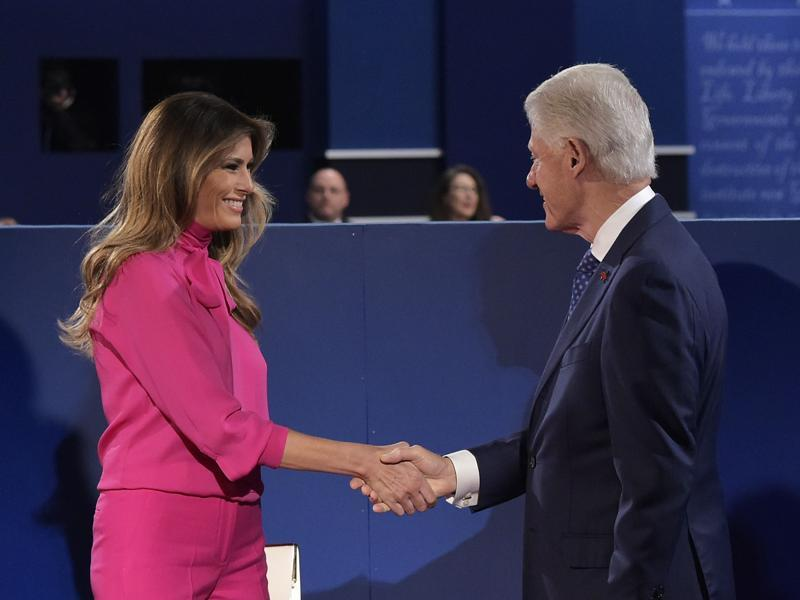 Bill Clinton checks hands with Melania Trump at Washington University. (AFP Photo)