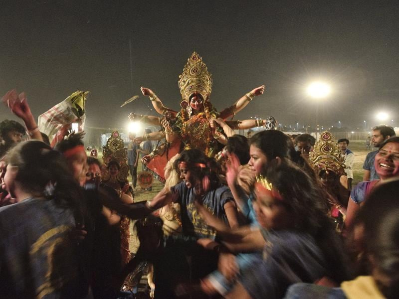 Devotees celebrate as they prepare to immerse an idols of Goddess Durga in River Yamuna. (Gurinder Osan/HT PHOTO)