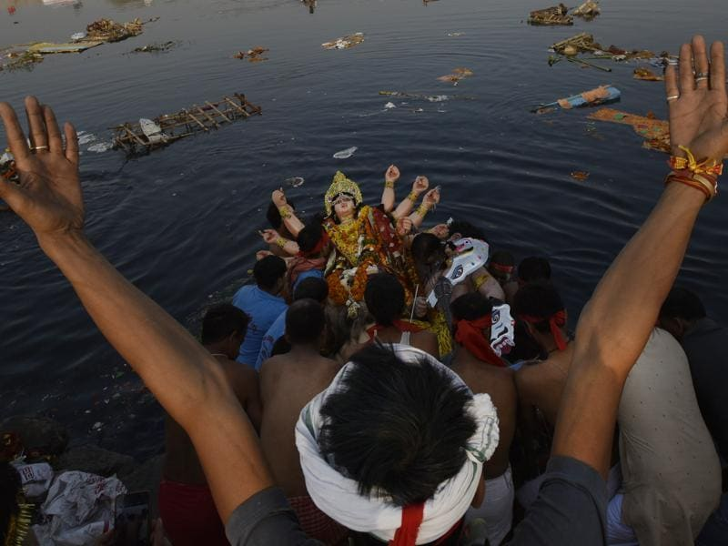 Devotees immersing idols of Goddess Durga in River Yamuna in New Delhi on Tuesday.  (Ravi Choudhary/HT PHOTO)