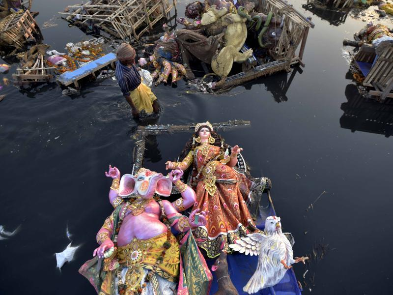 Locals scavenge for the valuable or useful remains amid idols of goddess Durga in river Yamuna near ISBT in New Delhi on October 12, 2016. (Ravi Choudhary/HT PHOTO)