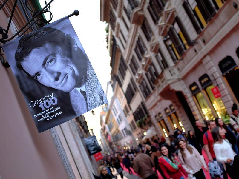 People walk by a portrait of late US actor Gregory Peck through Via Condotti, partly covered by a red carpet, on October 18, 2016 in Rome during a series of events during the 11th Rome Film Festival marking the centenary of the birth of Gregory Peck.  (AFP)