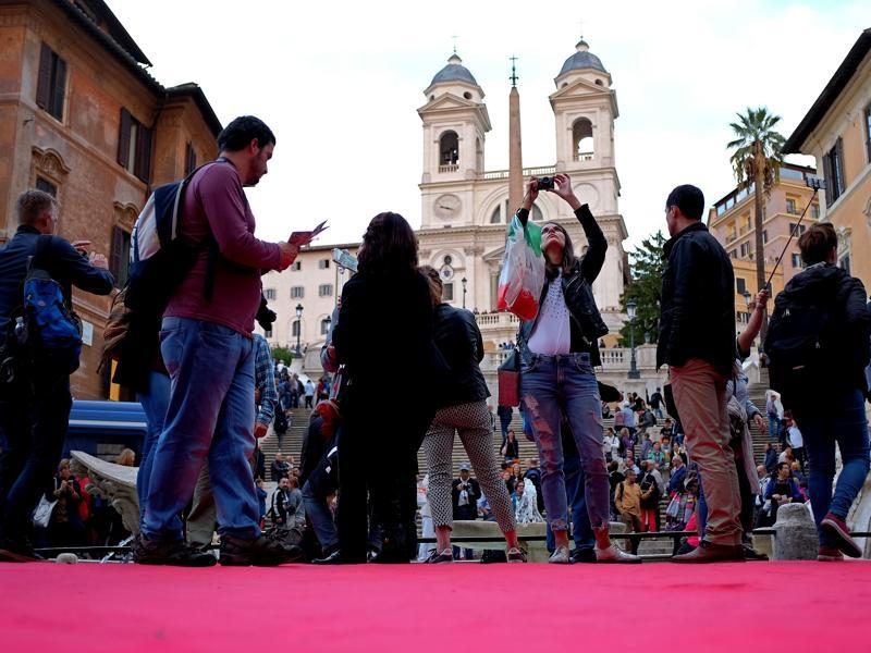 Tourists standing on Spanish square, partly covered by a red carpet, take photos of the Spanish Steps, with the Trinita dei Monti church in background. (AFP)