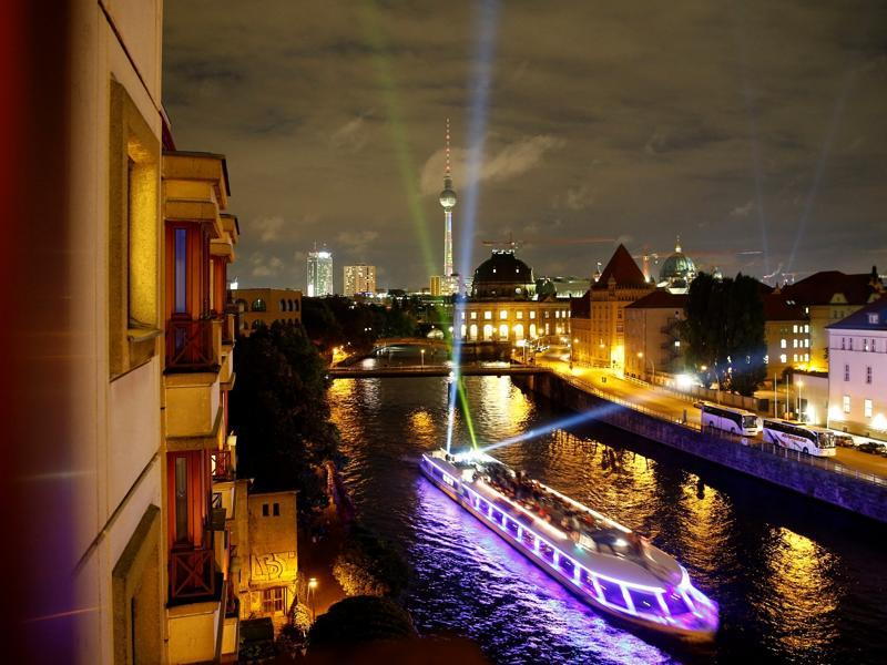 A boat with spotlights sails the Spree river during the opening day of the