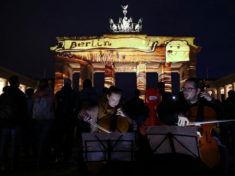 Musicians from Hungary play their instruments as the Brandenburg Gate is illuminated during the Festival of Lights. (REUTERS)