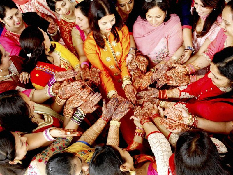 Teachers show their henna-applied hands during the Karva Chauth celebrations at a school in Reetkheri in Patiala. (PTI)