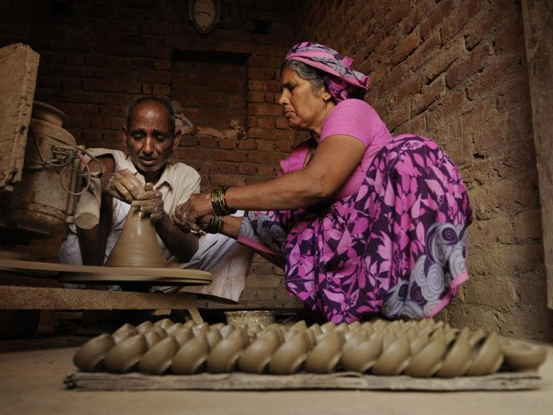 Though wax candles and electric lights have outdone the earthen lamps  in illuminating homes on Diwali, many potters' families are still keeping the tradition alive hoping that these will make a comeback. (Burhaan Kinu/HT PHOTO)