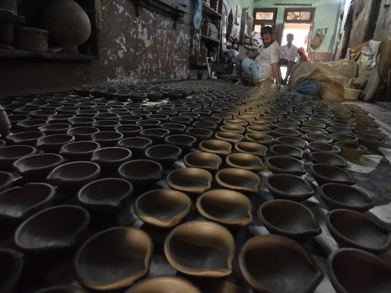 As the demand spikes during Diwali, potters churn out more diyas. Roadside stalls crop up in many markets just selling diyas and candles.  (Sanjeev Verma/HT Photo)