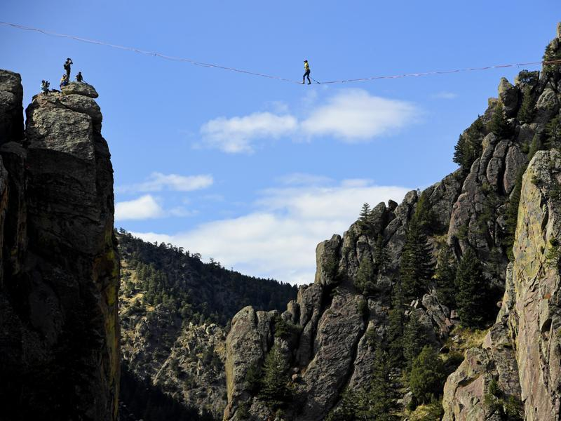Taylor VanAllen, 24, makes the First Across, or FA, on a high-line from the Wind Tower rock formation to the Bastille rock formation, 450 feet off the ground, in Boulder, Colorado. VanAllen, an athlete with Slackline Industries, recreated the Ivy Baldwin high line crossing of Eldorado Canyon in a benefit for trail building at the state park.  (AP)