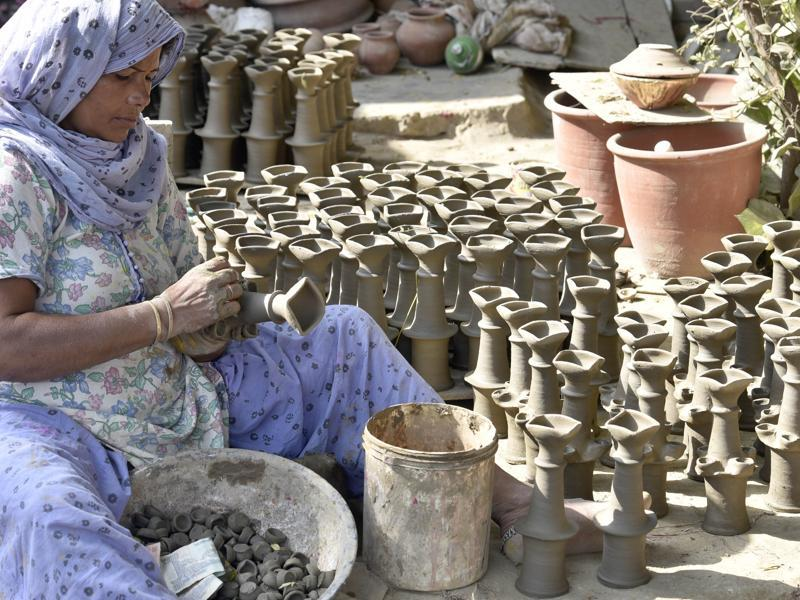 A potter makes earthen lamps for Diwali in Amritsar on Monday. (Gurpreet Singh/HT Photo)