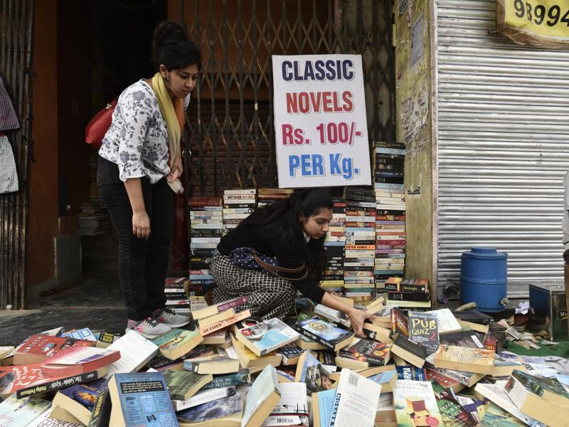 Committed book lovers  sort book stacks to find hidden gems  of limited edition books at the Sunday bazaar. (Vipin Kumar/HT PHOTO)