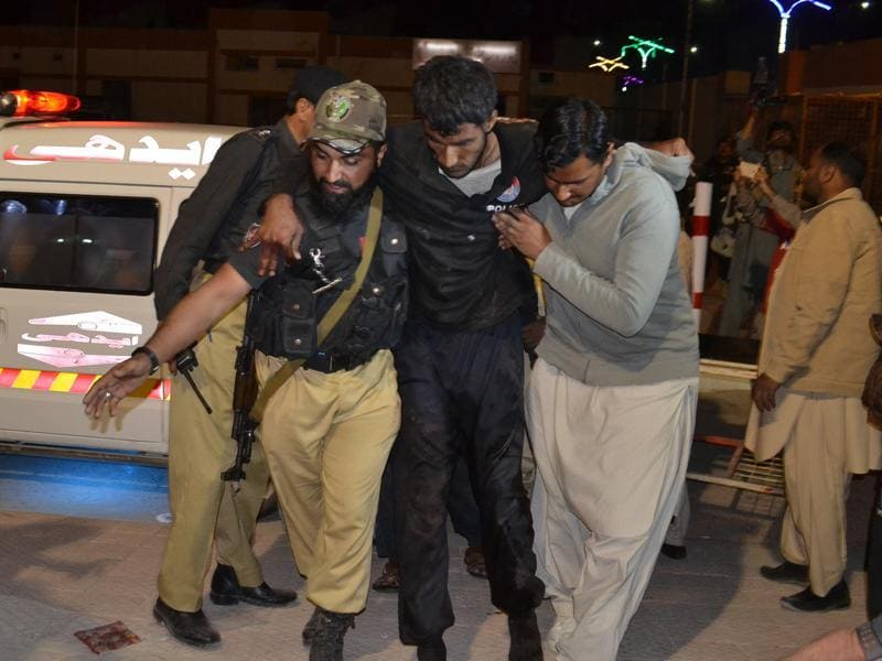 A Pakistani volunteer and a police officer rush an injured person to a hospital in Quetta (AP)