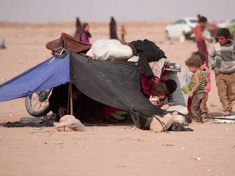 Refugees rest under a makeshift tent near the Iraqi border in Hasaka Governorate. (Reuters)