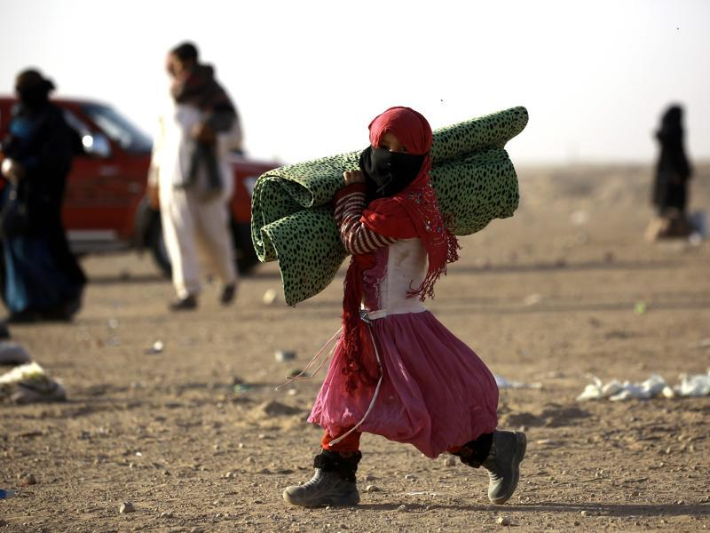 An Iraqi refugee girl who fled Mosul, the last major Iraqi city under the control of the Islamic State (IS) group, due the Iraqi government forces offensive to retake the city, walks carrying a blanket in the desert area of Rajam al-Saliba on the Iraq-Syria border south of al-Hol in Syria's Hassakeh province. (AFP)