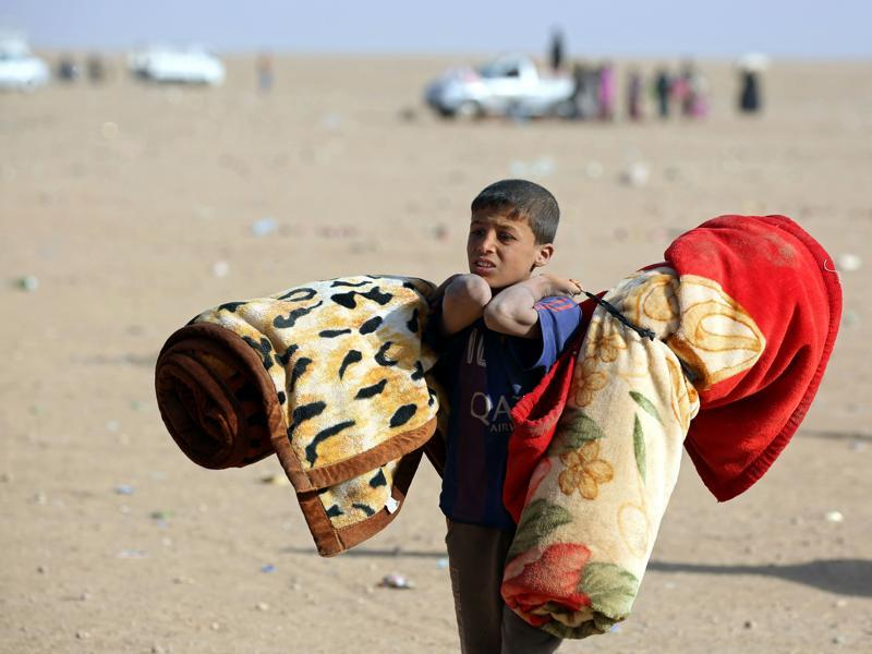 An Iraqi refugee boy who fled Mosul carries blankets following his arrival in the desert area of Rajam al-Saliba on the Iraq-Syria border south of al-Hol in Syria's Hassakeh province. (AFP)