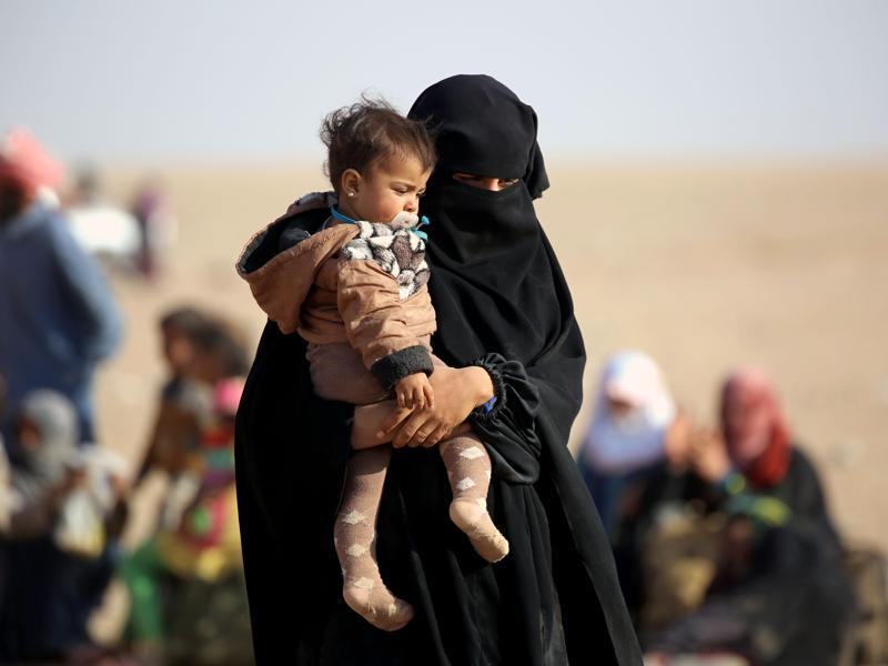 An Iraqi refugee woman who fled Mosul walks with her child as they wait to enter Syria in the desert area of Rajam al-Saliba on the Iraq-Syria border south of al-Hol in Syria's Hassakeh province. (AFP)