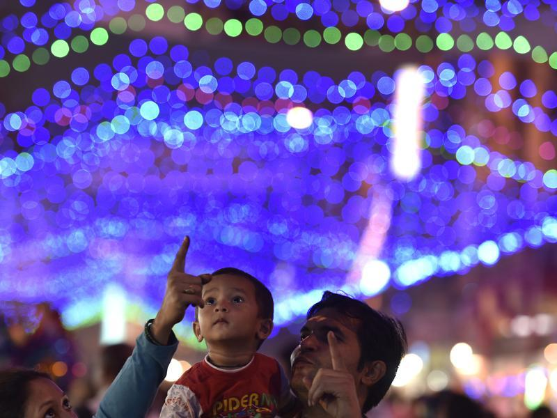 A family enjoys illuminated markets during the Dhanteras festival in New Delhi on Friday. (Raj K Raj/HT PHOTO)