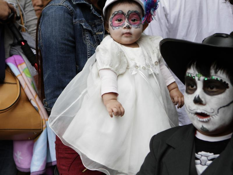 Six-month-old Melody, dressed as a calavera, is carried by her mother through the crowd that is gathering for the start of the Gran Procession of the Catrinas. (AP)
