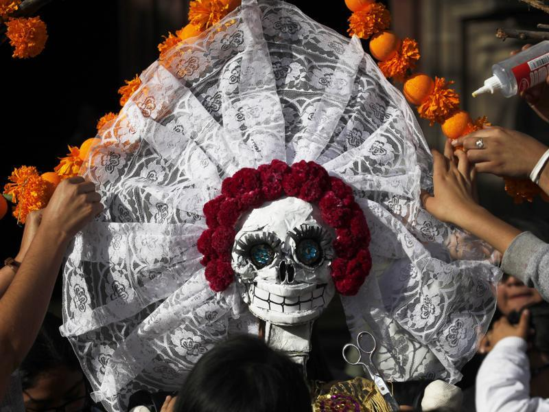 The holiday honours the dead as friends and families gather in cemeteries to decorate their loved ones' graves and hold vigil through the night on November 1 and 2.  (AP)
