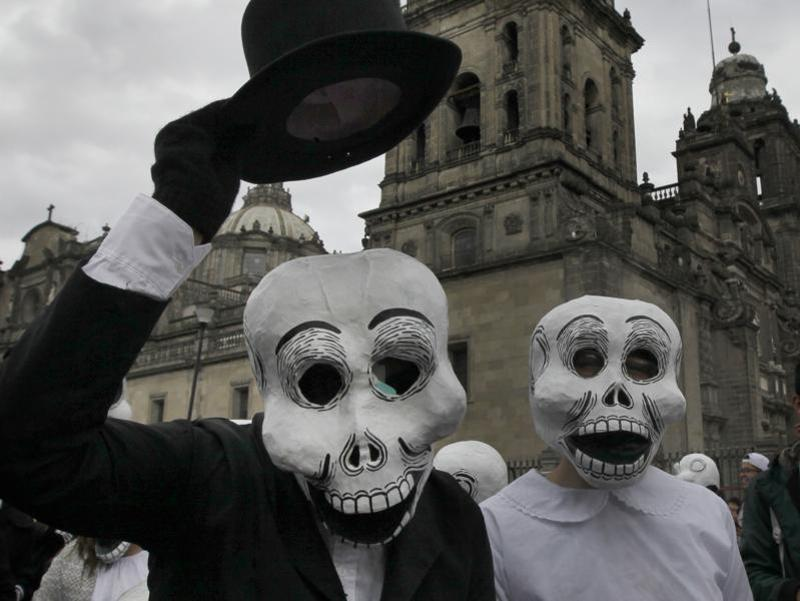 A couple wearing skull masks perform at the festival. (AP)