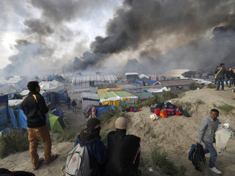Smoke rises as migrants and journalists look at burning makeshift shelters and tents in the 'jungle' on the third day of their evacuation and transfer to reception centres in France, as part of the dismantlement of the camp in Calais. (Reuters Photo)