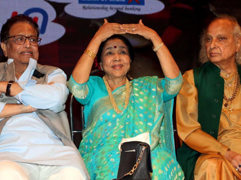 Playback singer Asha Bhosle gestures as Indian classical vocalist Pandit Jasraj (R) and Hridaynath Mangeshkar (L) look on at the Hridaynath Mangeshkar Awards in Mumbai. (AFP Photo)