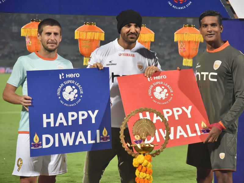 John Abraham, Bollywood actor and owner of Northeast United FC (NEUFC) with NEUFC forward Emiliano Alfaro (L) and Goalkeeper Subrata Paul, lights lamp on the eve of Diwali celebrations before a football match in Guwahati. (PTI Photo)