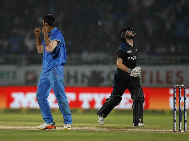 New Zealand's captain Kane Williamson, right, reacts after India's Axar Patel, left, dismissed him. (AP photo)