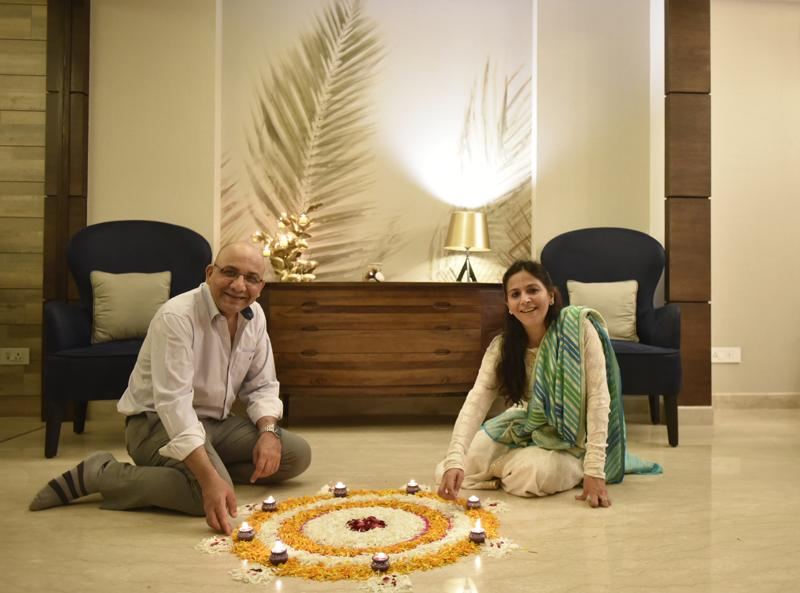 The couple lighting diyas around the rangoli they've created  at the entrance in the ground floor. (Ravi Choudhary/HT PHOTO)