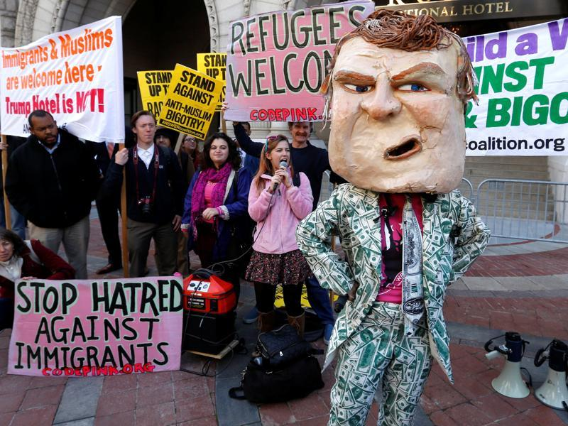 A demonstrator dresses in a Trump costume as people gather to protest against Republican US presidential nominee Donald Trump on the sidewalk, outside the grand opening of his new Trump International Hotel in Washington. (Reuters Photo)