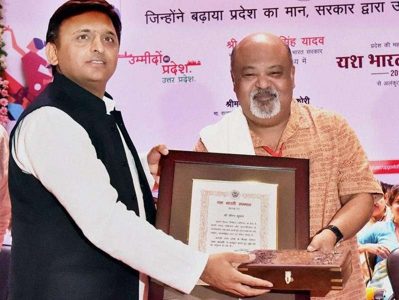 Uttar Pradesh Chief Minister Akhilesh Yadav honours Bollywood actor and director Saurabh Shukla with Yash Bharti Samman in Lucknow. (PTI Photo)
