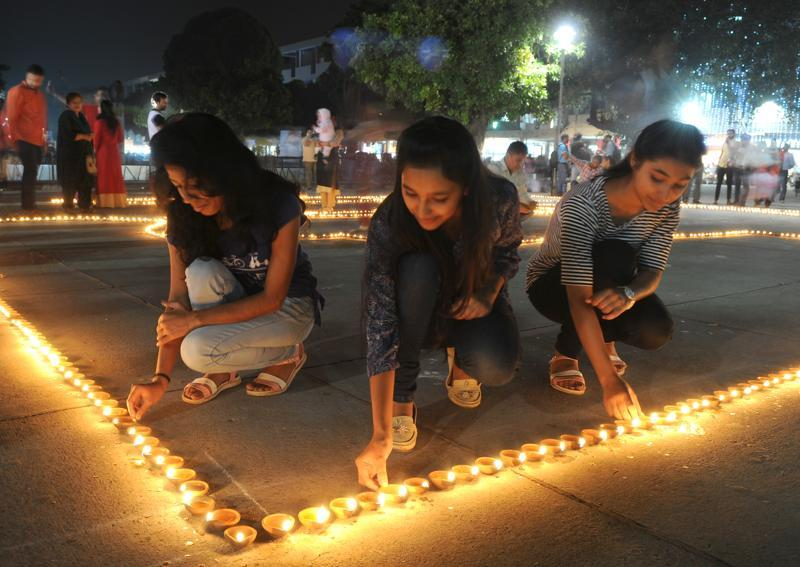 Young women lighting diyas at the plaza in Sector 17, Chandigarh. (Anil Dayal/HT Photo)