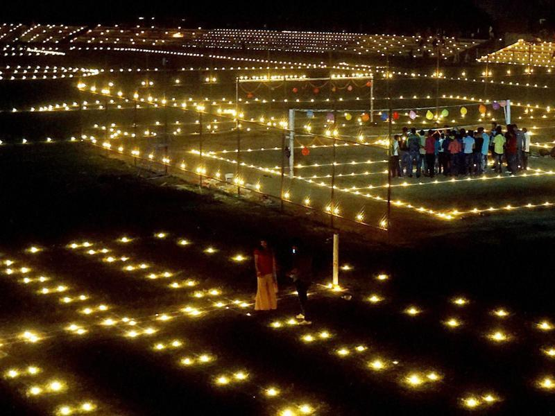 Sportspersons light candles to pay tribute to Indian soldiers  on the eve of Diwali at a stadium in Varanasi on Saturday. (PTI)