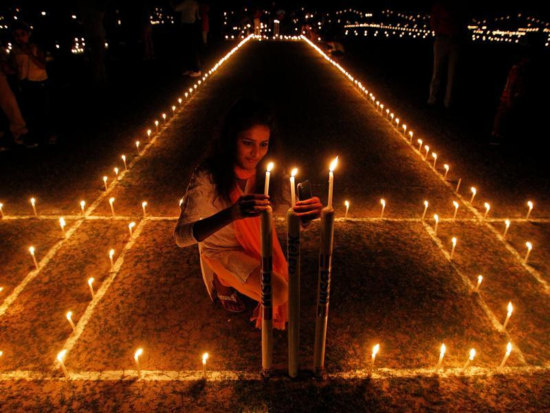 A girl lights candles inside a cricket stadium on the eve of Diwali, in Allahabad on Saturday. (Reuters)
