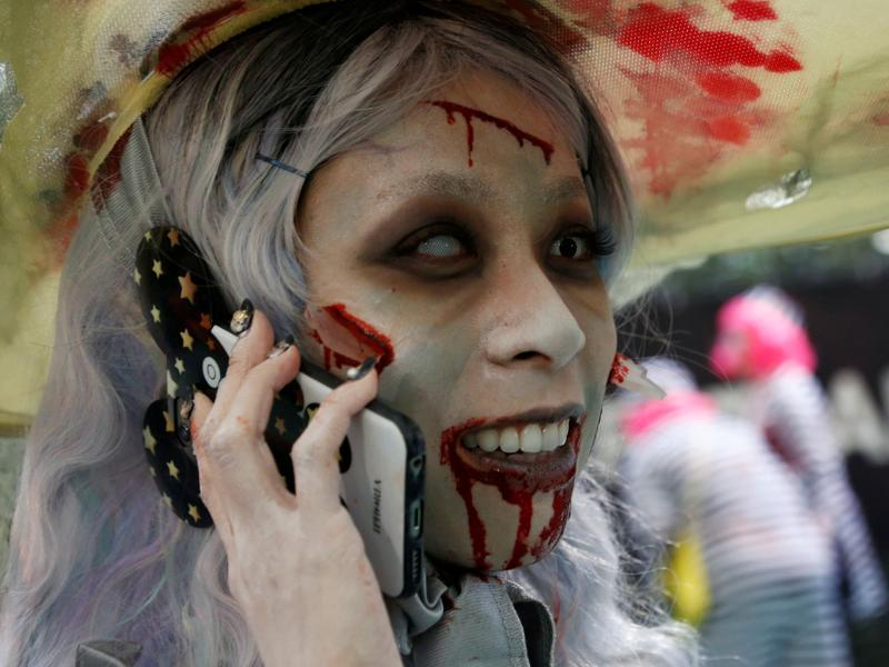 A Kawasaki participant in costume is busy with her phone. (REUTERS)