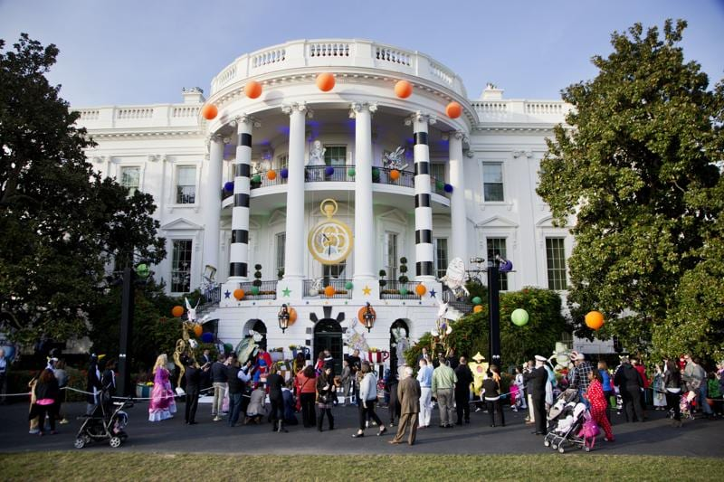 US President Barack Obama and the first lady Michelle Obama hand treats as they welcome children from Washington area and children of military families to trick-or-treat celebrating Halloween at the South Portico of the White House. (AP Photo)