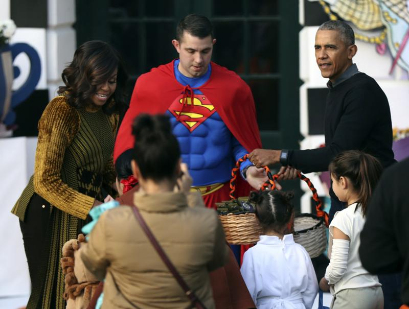 President Barack Obama and first lady Michelle Obama hand out treats as they welcome children for the trick-or-treat celebration on Halloween at the South Portico of the White House. (AP Photo)
