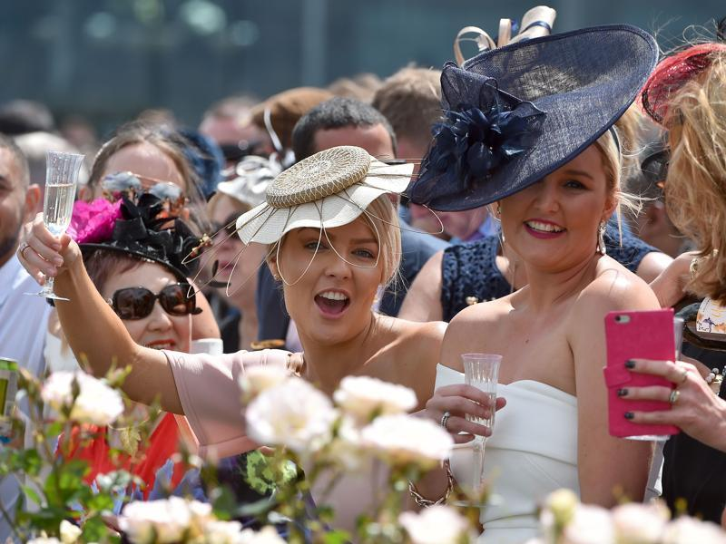Horses, drinks, sunshine and hats make for a fascinating time. Racegoers react as the horses prepare to take to the track during the Melbourne Cup. (AFP)