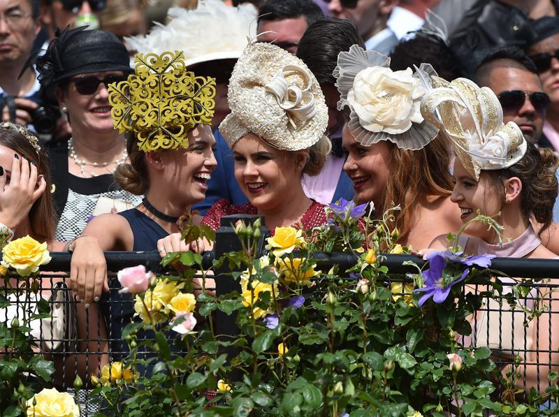 Girls like hats, no matter what the design. Racegoers react during the event. (AFP)