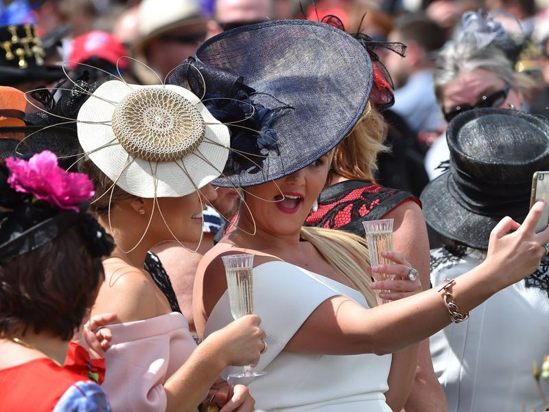 Racegoers pose for a selfie. (AFP)