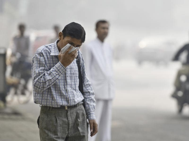 A man covers his face with a  handkerchief in a feeble attempt to protect against the pollution.  Masks with air filters are recommended for people who are susceptible to wheezing or other health conditions that get aggravated due to the bad air quality.  (Raj K Raj/HT PHOTO)