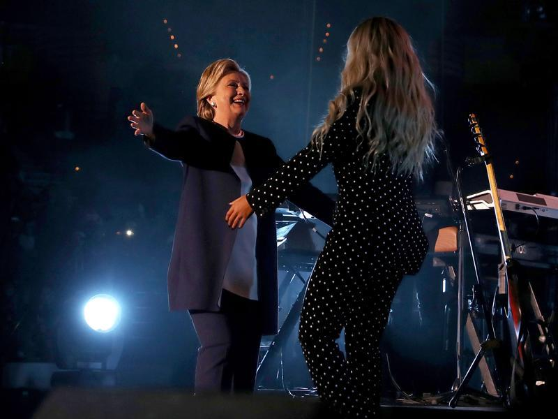 Democratic presidential nominee former Secretary of State Hillary Clinton greets recording artist Beyonce during a Get Out The Vote concert at Wolstein Center on November 4, 2016 in Cleveland, Ohio.  (AFP)