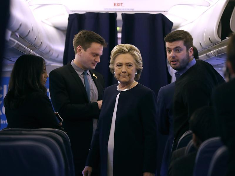 Democratic presidential nominee former Secretary of State Hillary Clinton talks with members of her staff aboard her campaign plane at Westchester County Airport on November 4, 2016 in White Plains, New York. (AFP)