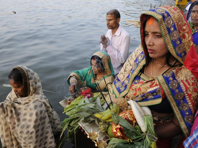 Devotees performing rituals to pay reverence to Lord Surya, the sun god,  during Chhath Puja at upper lake in Bhopal.  (Mujeeb Faruqui/HT PHOTO)