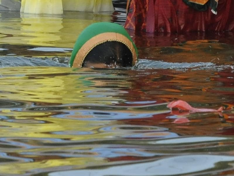 A lady taking a holy dip to pay reverence to Lord Surya . (Mujeeb Faruqui/HT PHOTO)