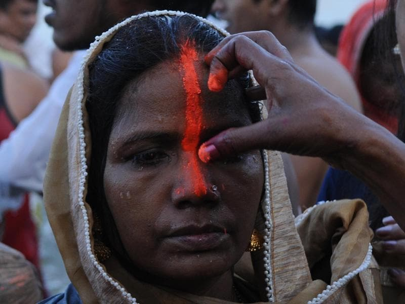 A devotee is marked with vermillion during Chhath celebrations at the banks of Hooghly.   (Subhankar Chakraborty/HT PHOTO)